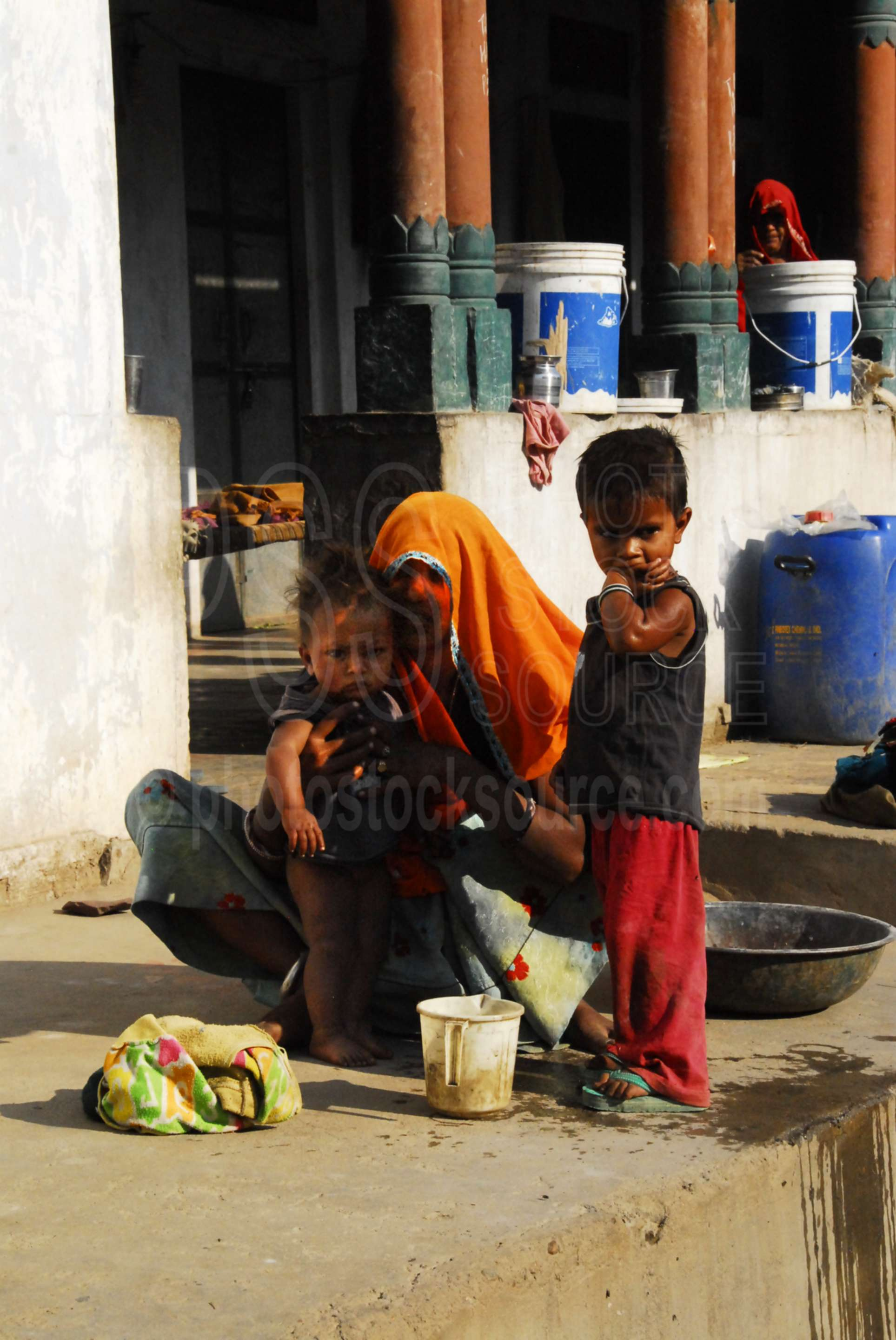 Woman and Children,woman,morning,sitting,child,courtyard,village,cows