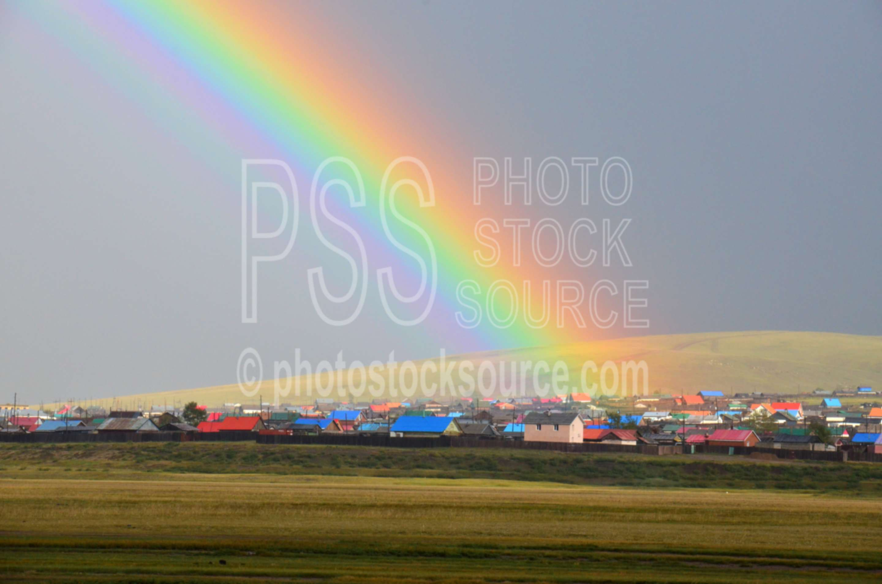 Rainbow over Kharkhorin,rainbow,town,houses,clouds,thunderstorm,weather,climate