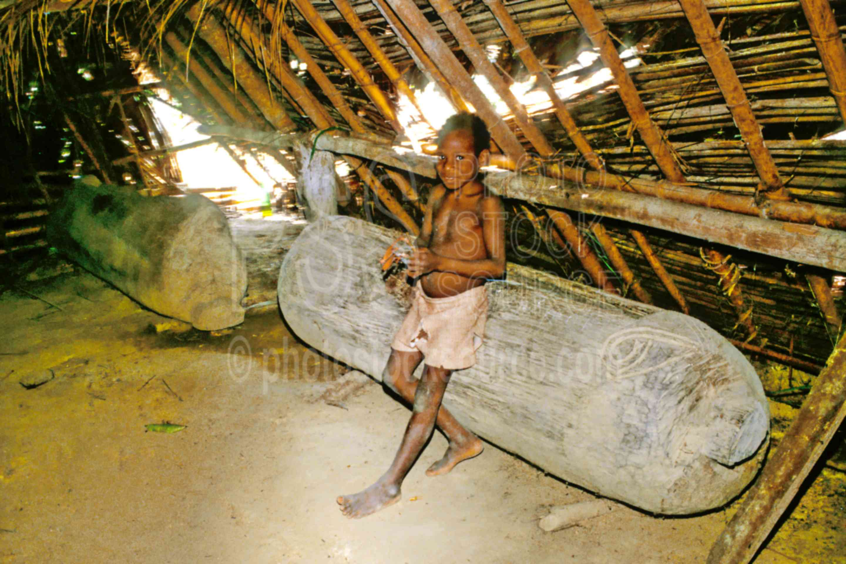 Boy and Garamut slit drum,arts,boys,carving,ceremony,drum,house,huts,ceremonies,children
