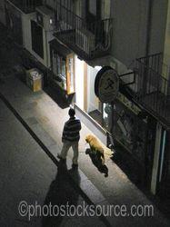 Photo of Man Walking Dog at Night